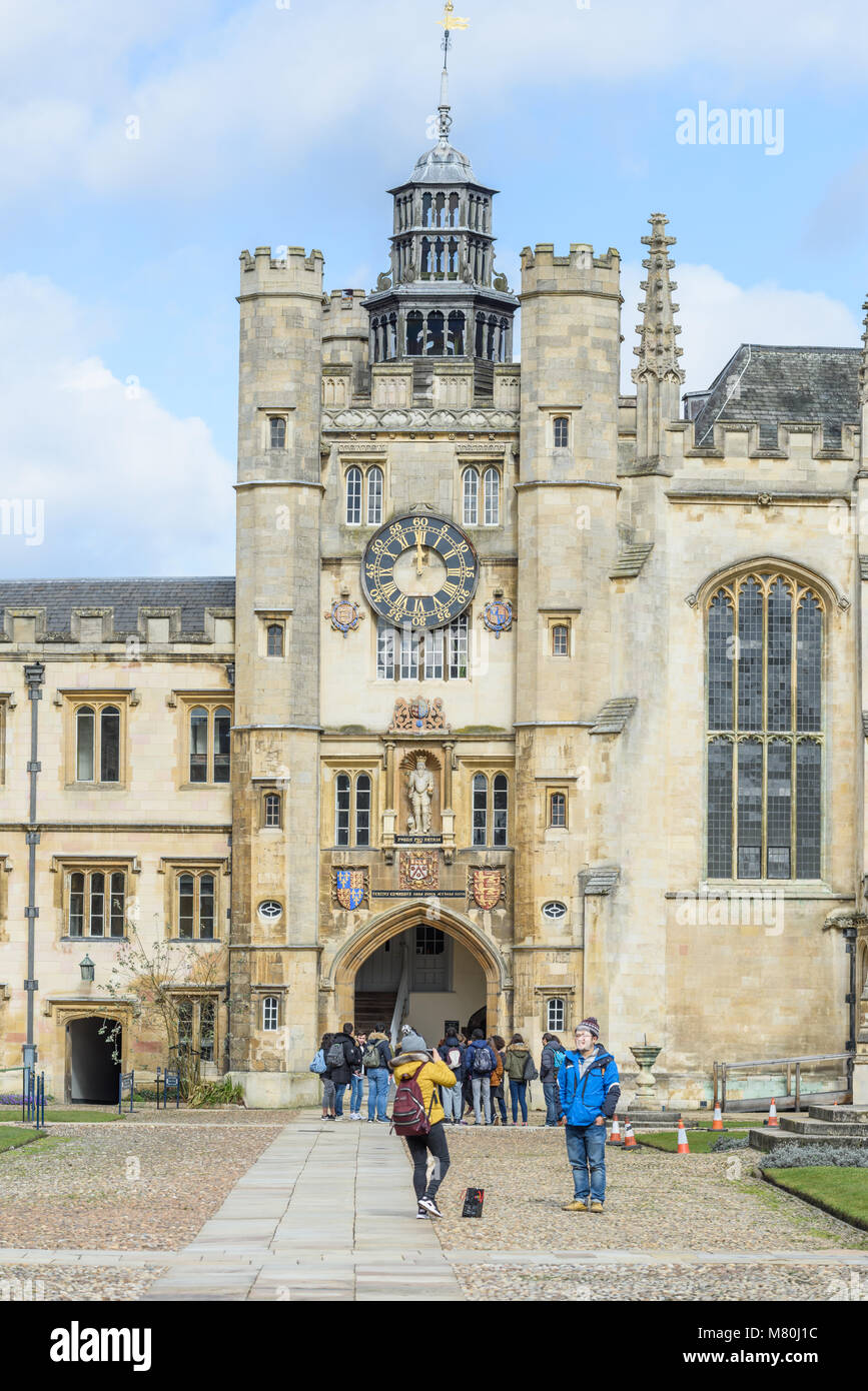 Tourists by the clock tower in the Great Court at Trinity college, Cambridge University, England, on a sunny winter - Stock Image