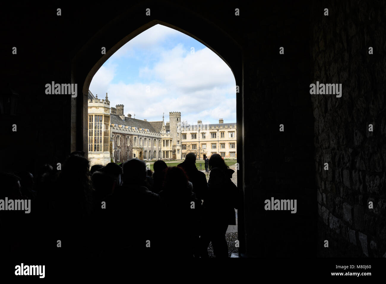 A group of school students in the Queens' Gate overlooking the Great Court at Trinity college, Cambridge University, - Stock Image