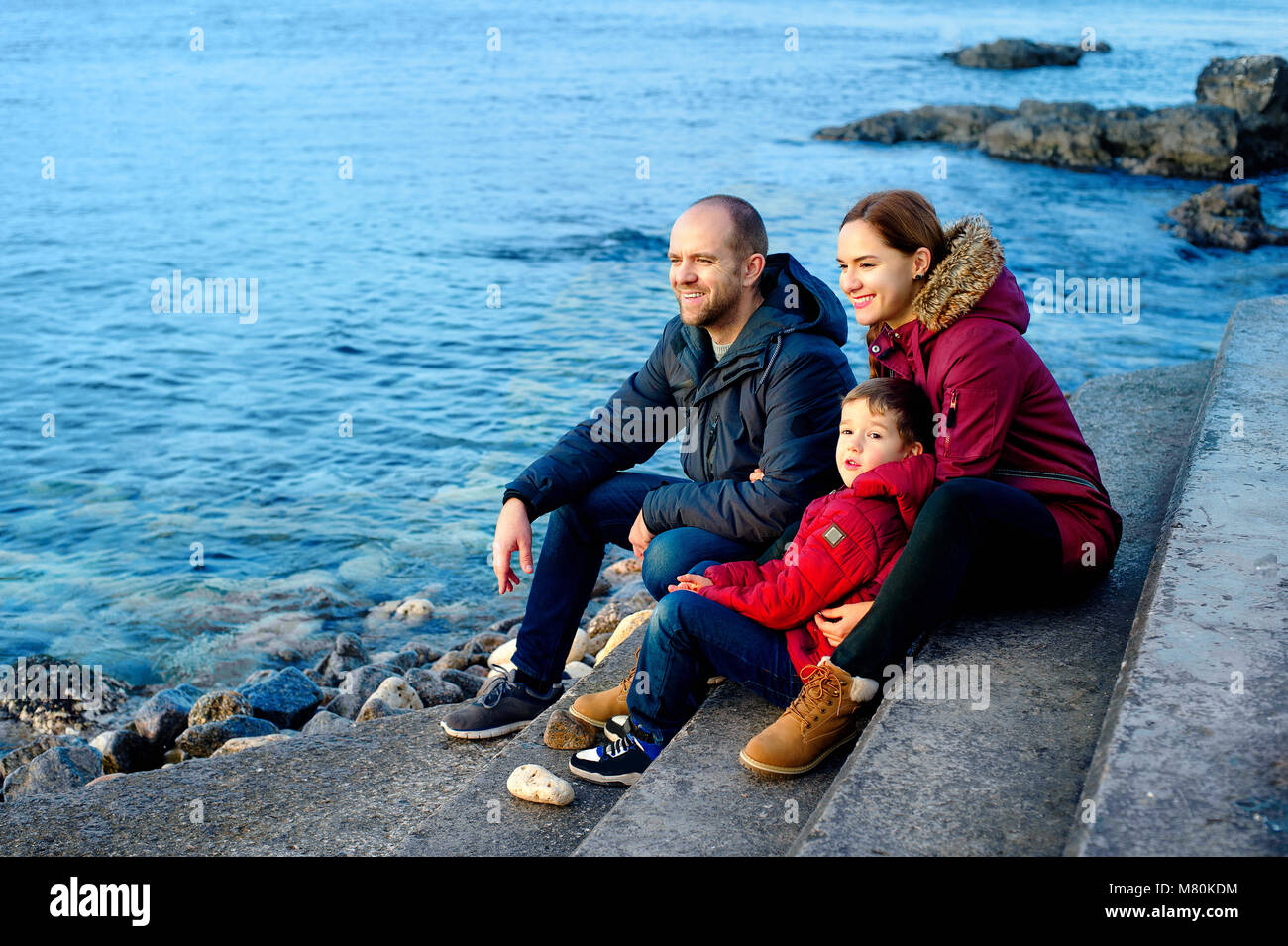family mom, dad and son are sitting on the beach by the sea and looking into the distance. Season - spring, autumn. - Stock Image