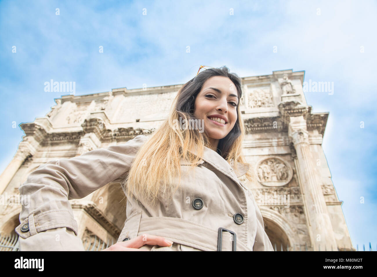 Low angle view of young pretty tourist woman smiling looking at camera, in background arch of Constantine monument - Stock Image