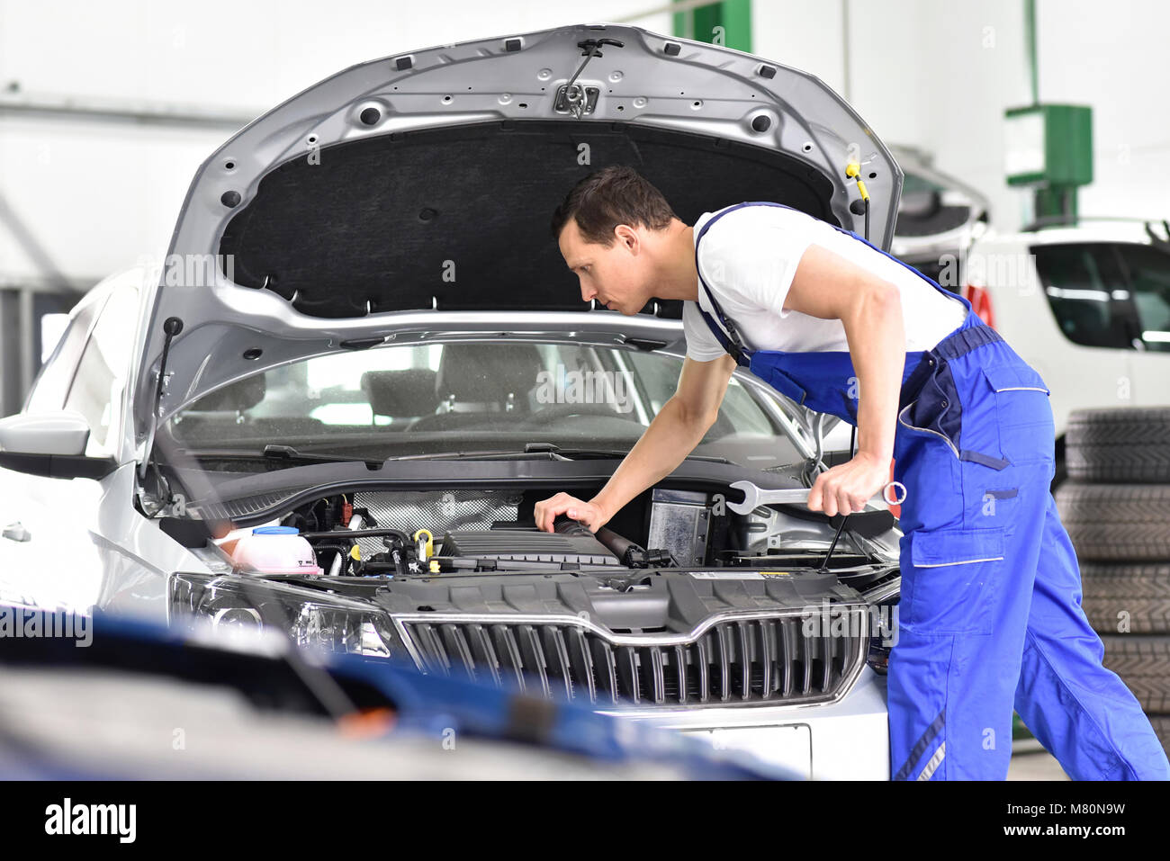 car mechanic in a workshop repairing a vehicle - Stock Image
