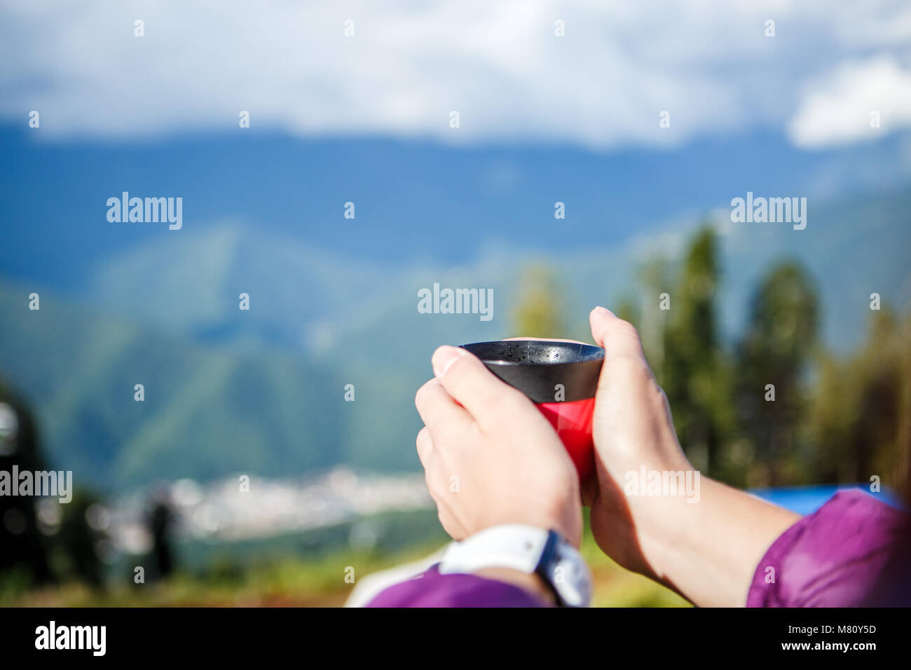 Photo of woman's hands with cup on blurred background of autumnal park - Stock Image