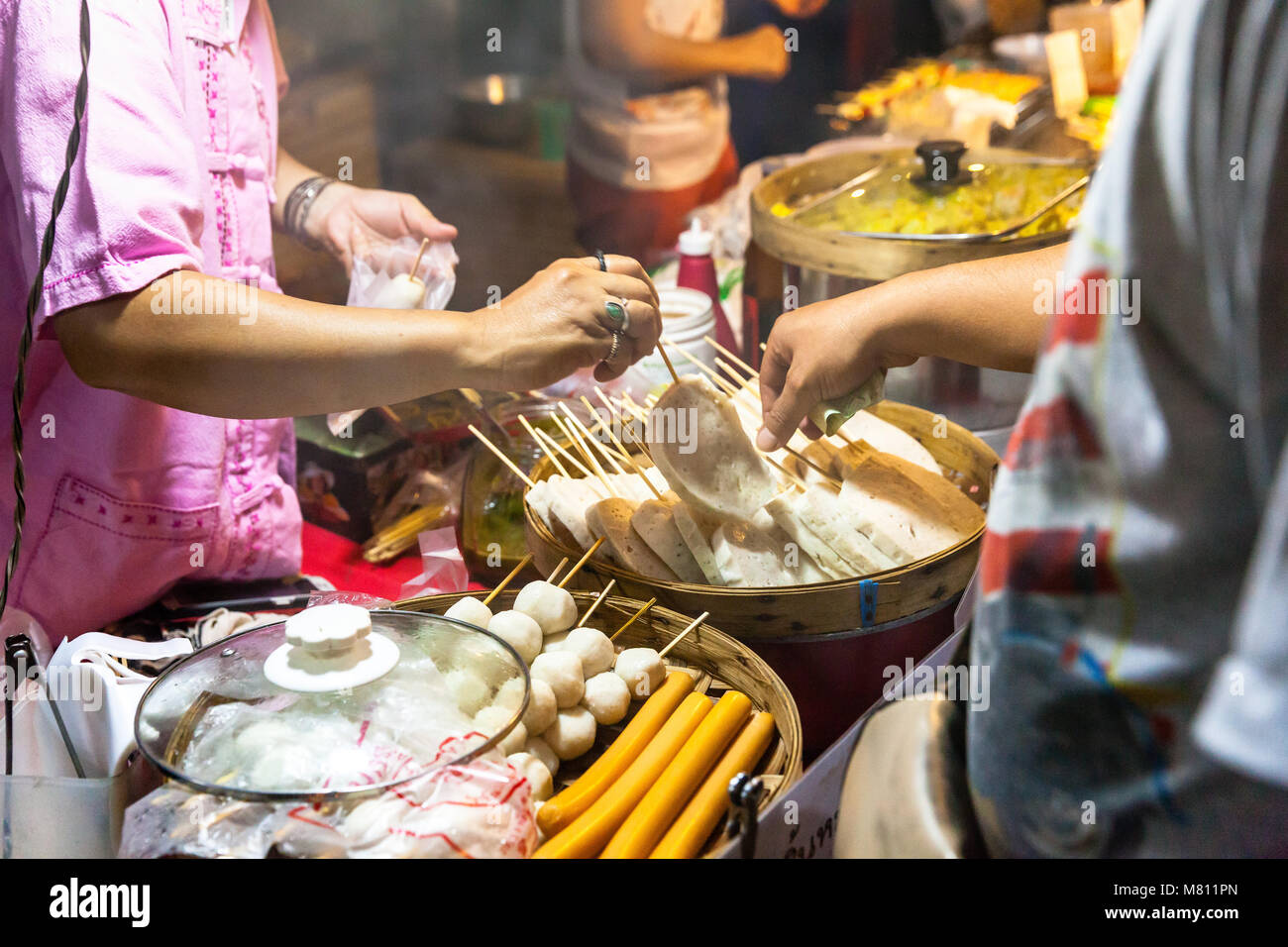 CHIANG MAI, THAILAND - AUGUST 21: Man buys street food at the Sunday Market (Walking Street) on August 21, 2016 - Stock Image