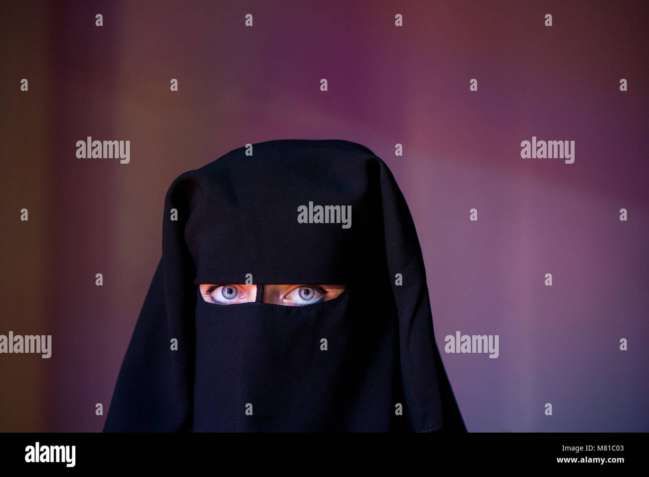 Arab woman with blue eyes with face covered with black niqab - Stock Image
