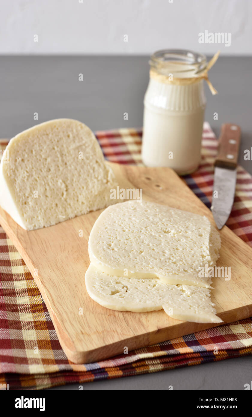 Ossetian cheese on a wooden cutting board - Stock Image