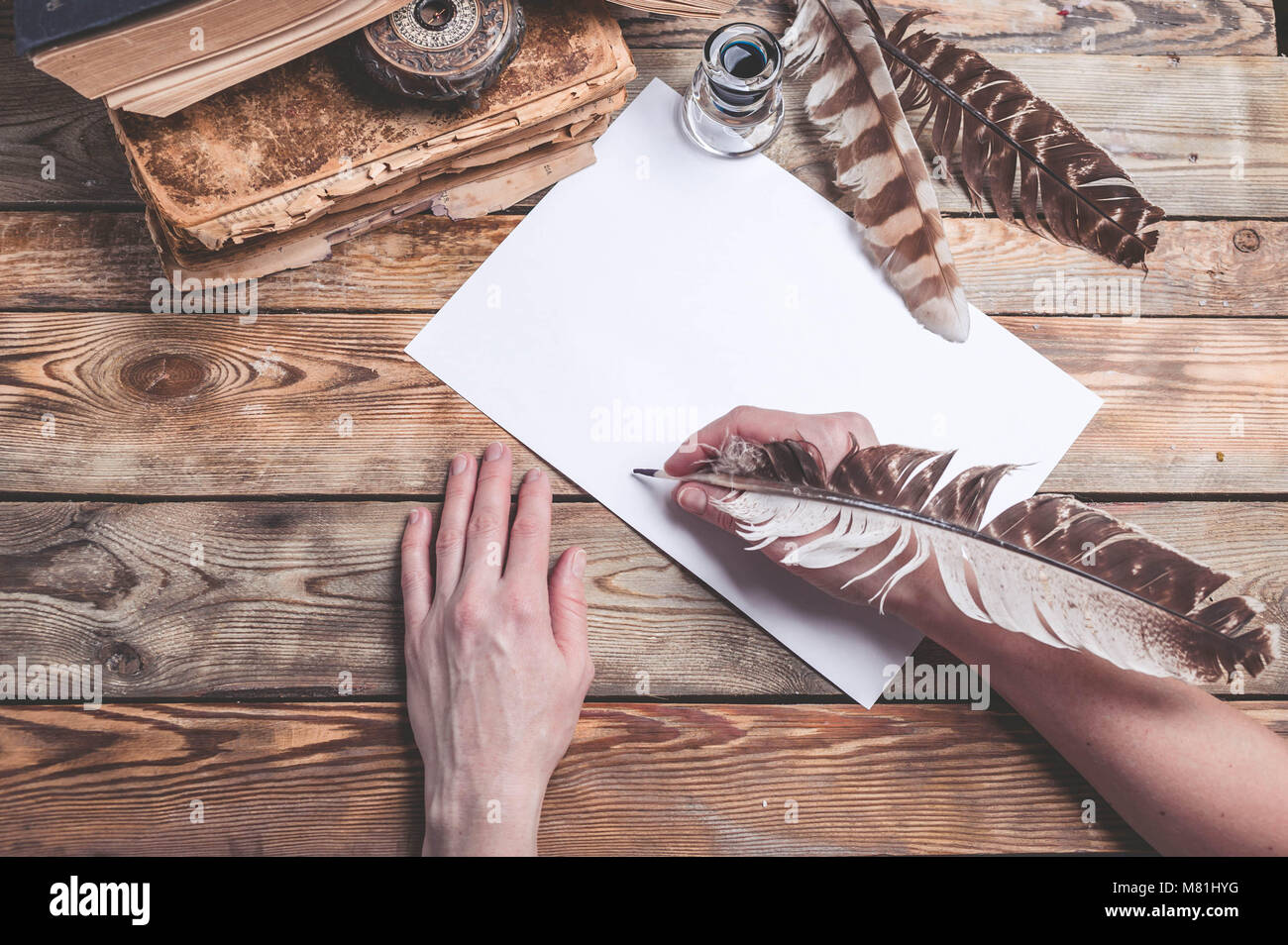The female hand writes the letter with feather quill pen. Old books, compass on a wooden background. Retro style - Stock Image