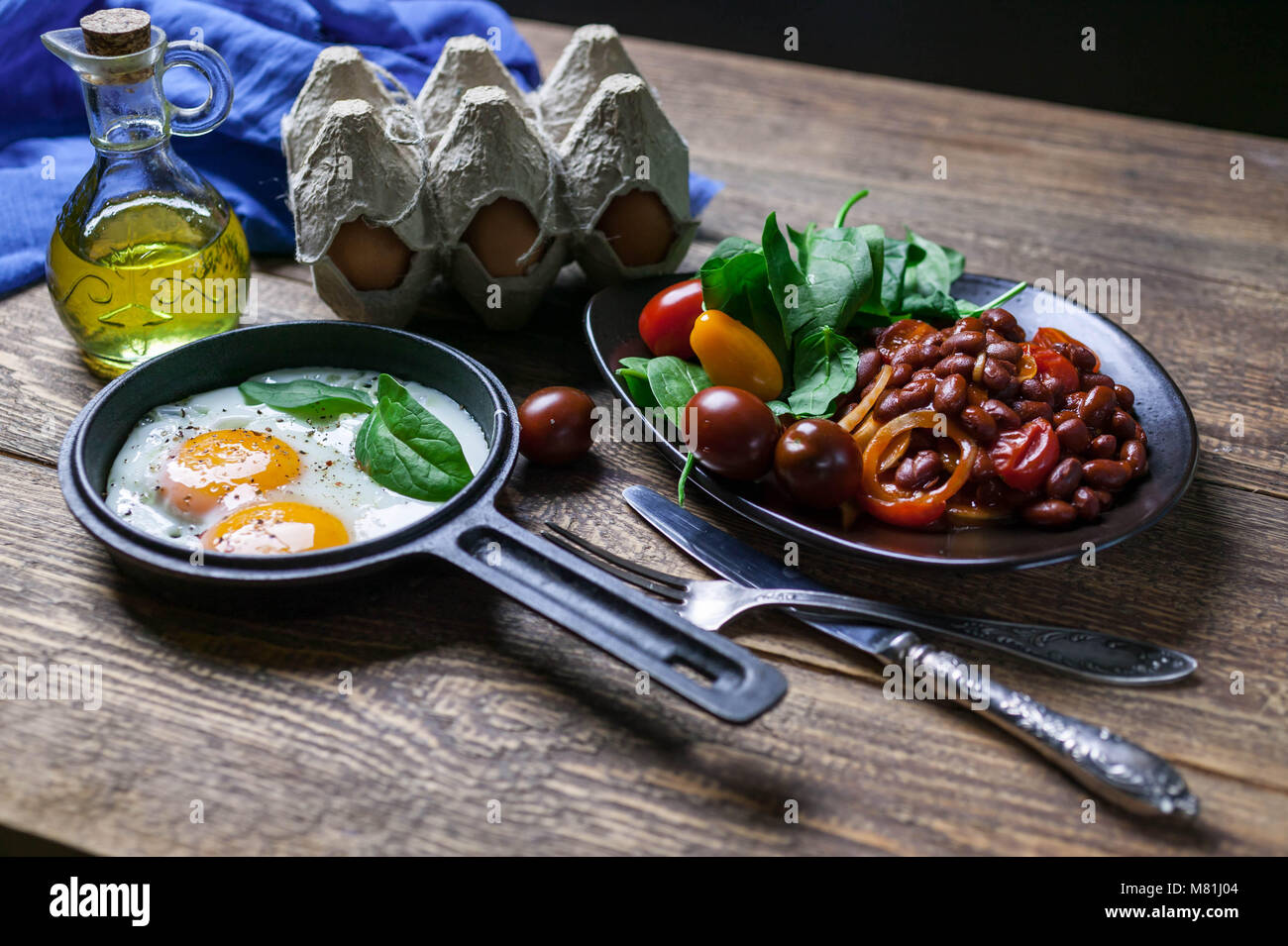 The pan fried eggs, haricot stewed in tomato sauce and fresh spinach. Concept of a healthy breakfast. Stock Photo