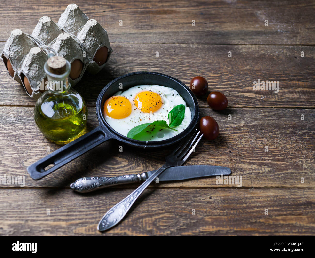 The pan fried eggs, cherry tomatoes and fresh spinach. Concept of a healthy breakfast. - Stock Image