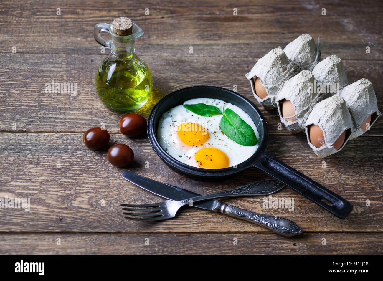 The pan fried eggs, cherry tomatoes and fresh spinach. Concept of a healthy breakfast. Stock Photo