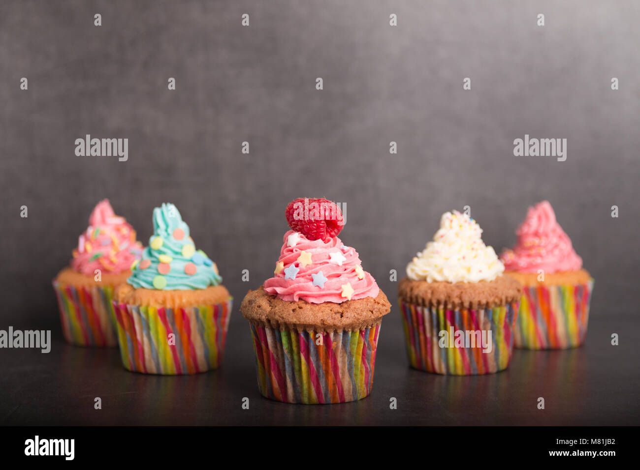 home baked cupcakes with colorful frosting and fruit - Stock Image
