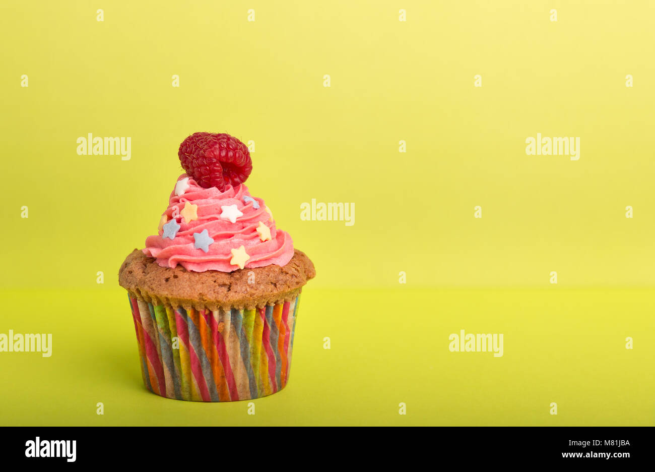 Home Baked Cupcakes With Colorful Frosting And Fruit On A Yellow Background