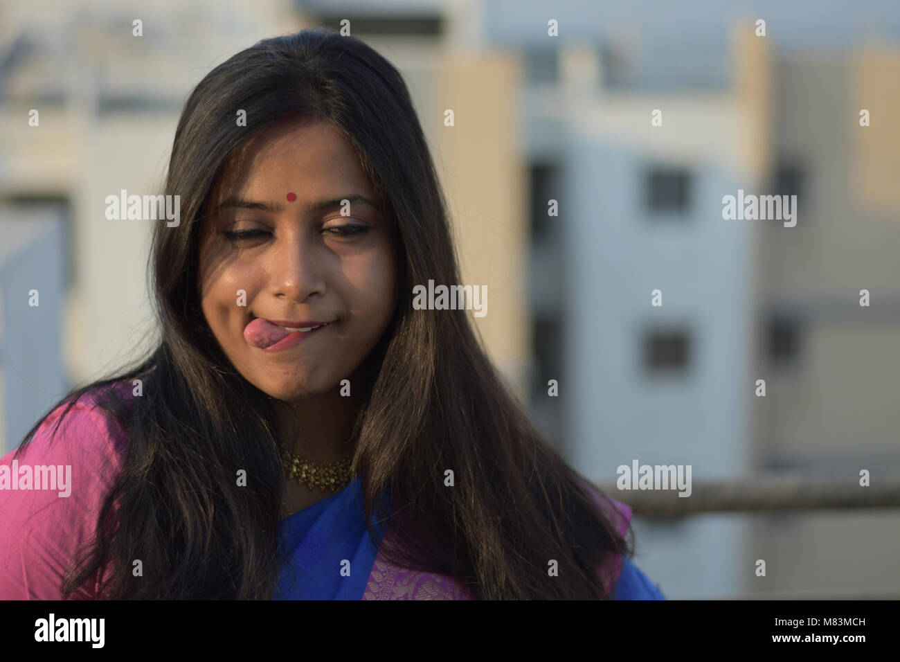 Beautiful young lady making face on rooftop outdoor - Stock Image