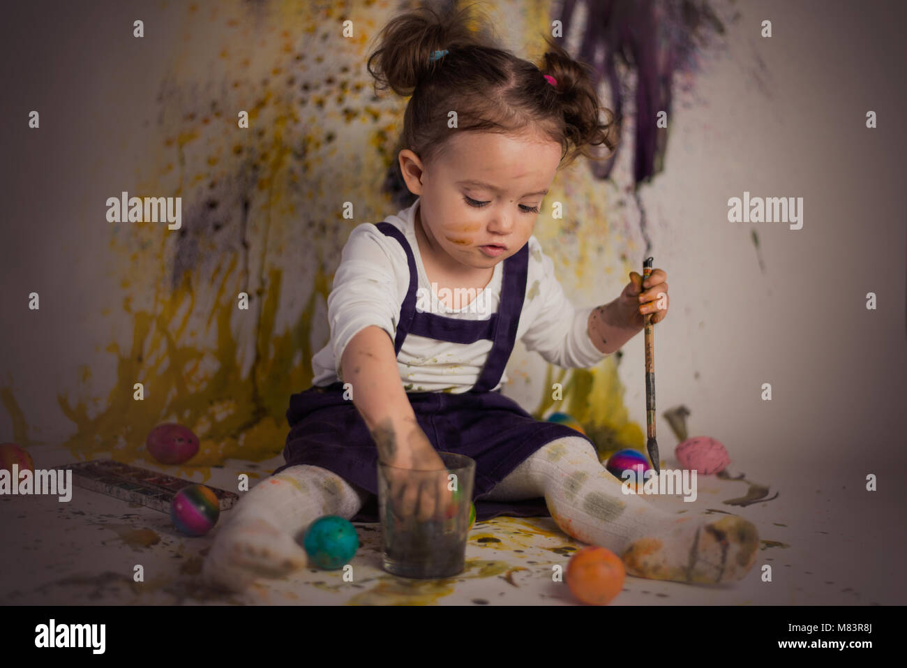 Little girl is painting easter eggs for easter. Stock Photo