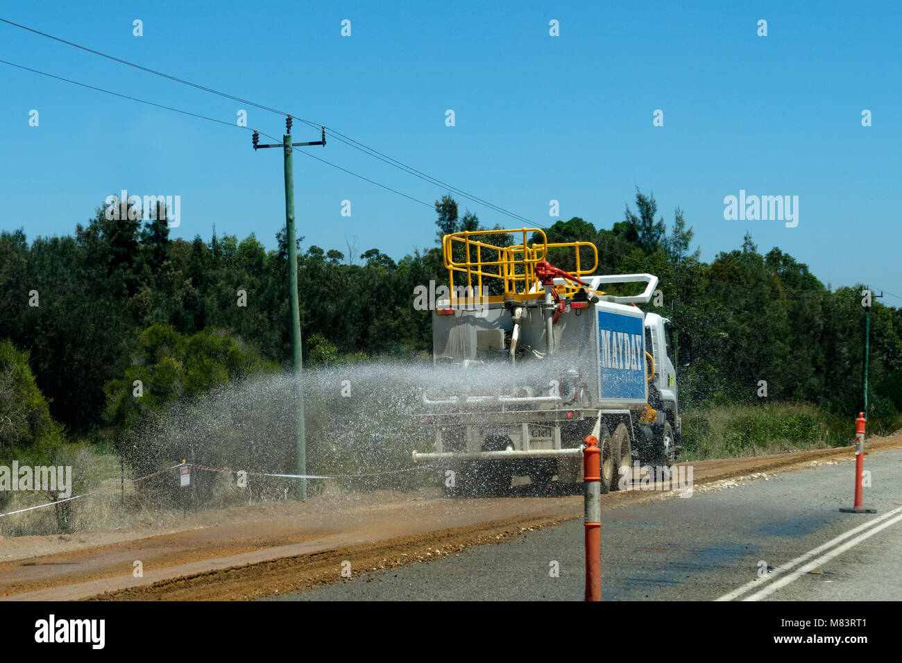 Water truck spraying water on road works, Perth, Western Australia Stock Photo