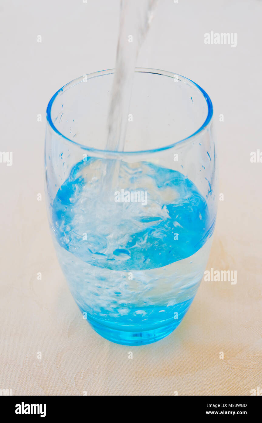 Pouring water in a blue glass. - Stock Image