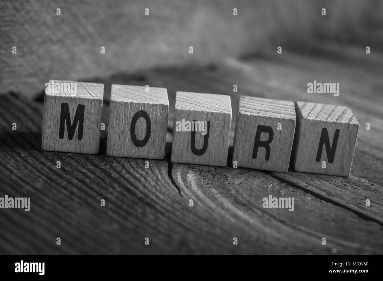 Macro Of The Word Mourn Formed By Wooden Blocks On A Wooden Floor - Stock Image
