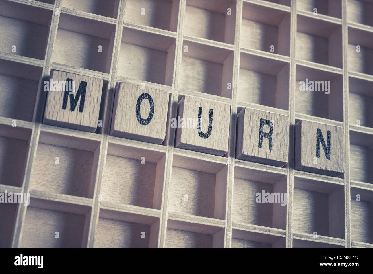 Closeup Of The Word Mourn Formed By Wooden Blocks On A Wooden Floor - Stock Image