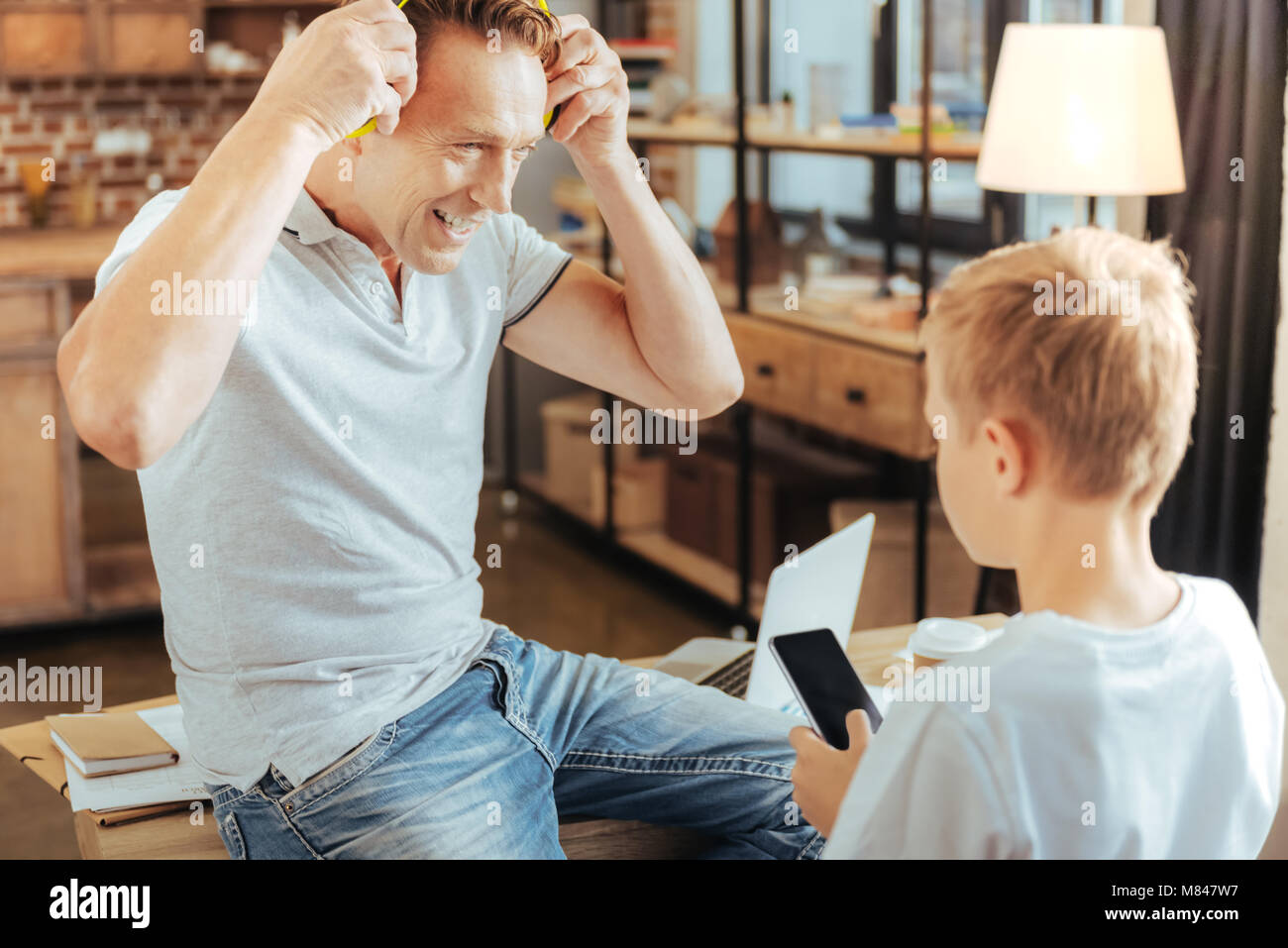 Positive handsome man putting on headphones - Stock Image
