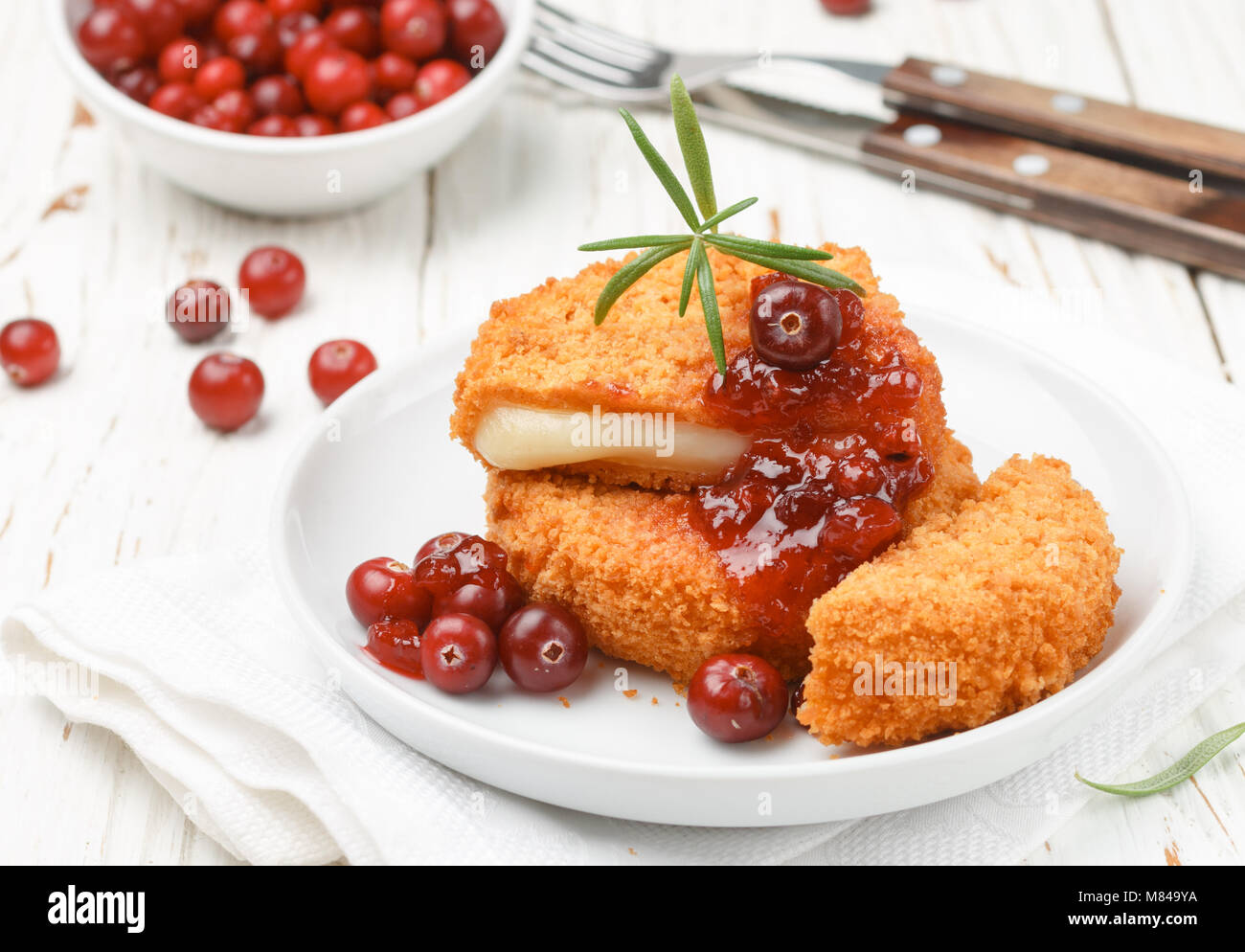 Baked Camembert (brie) with fresh berries and cranberry sauce with rosemary on a white plate. Gourmet appetizer. - Stock Image