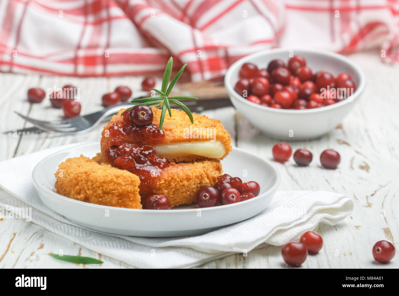 Baked breaded Camembert cheese (brie) with fresh berries and cranberry sauce with rosemary on a white background. - Stock Image