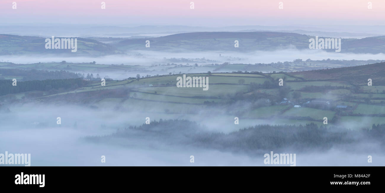 Rolling countryside at dawn shrouded in mist, Dartmoor National Park, Devon, England. Winter (December) 2017. - Stock Image