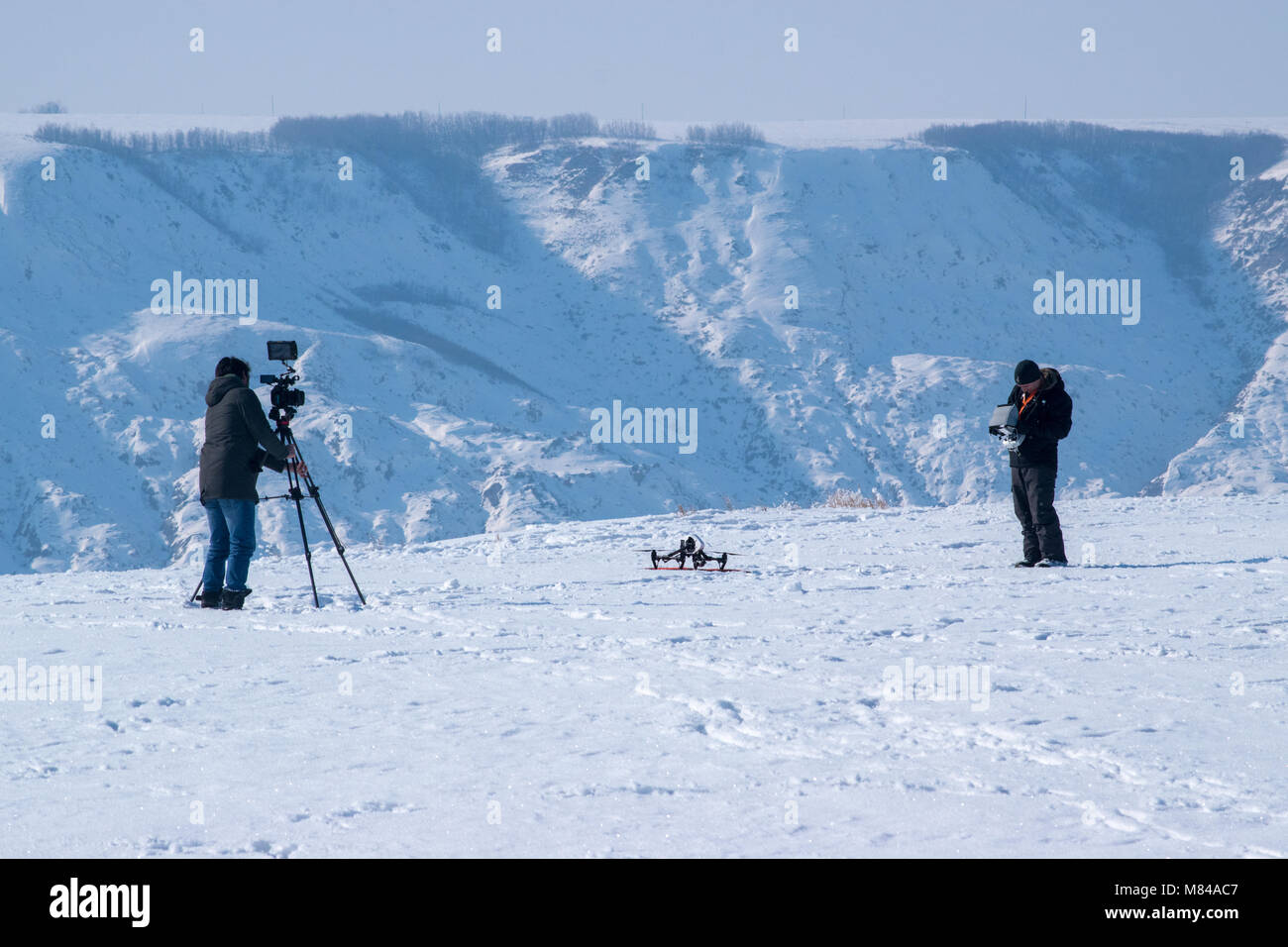 A camera man films a drone operator preparing to launch near Horsethief Canyon north of Drumheller, Alberta. Operating - Stock Image