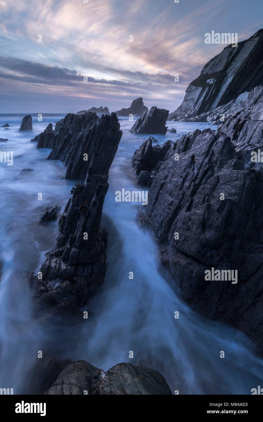 Twilight over the dramatic rocks of Ayrmer Cove, South Hams, Devon, England. Winter (January) 2018 - Stock Image