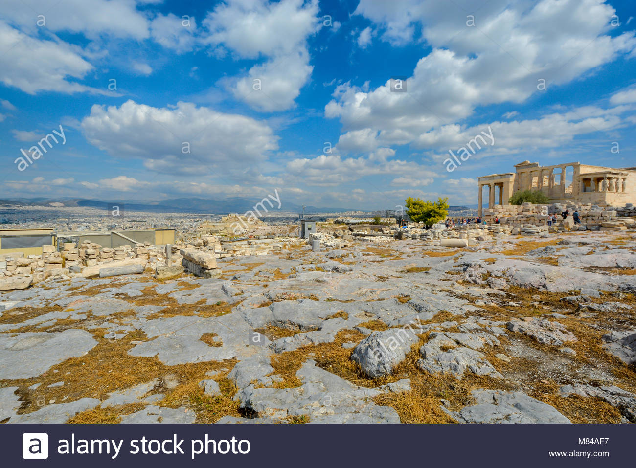 A warm summer day in Athens Greece as tourists enjoy the city view and explore the ancient Erechtheion on Acropolis - Stock Image