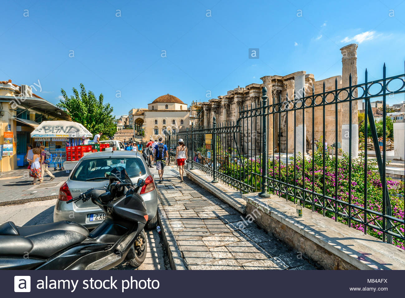 A couple enjoying a hot summer day in Athens Greece as they stroll on the street in front of the ancient wall of - Stock Image