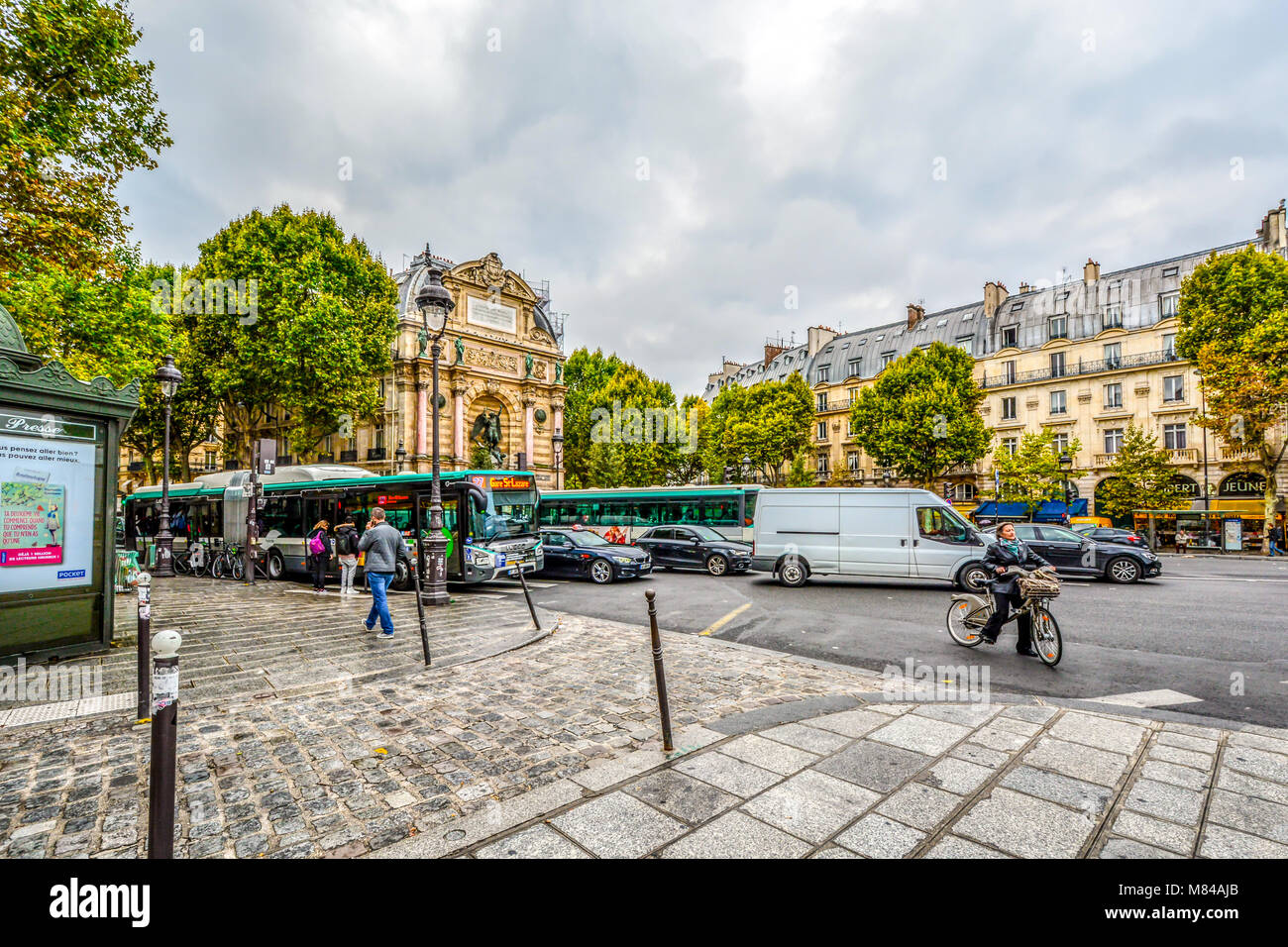 A cloudy, busy morning in Place Saint-Michel in the 5th arrondissement of Paris France with the Fontaine Saint-Michel - Stock Image