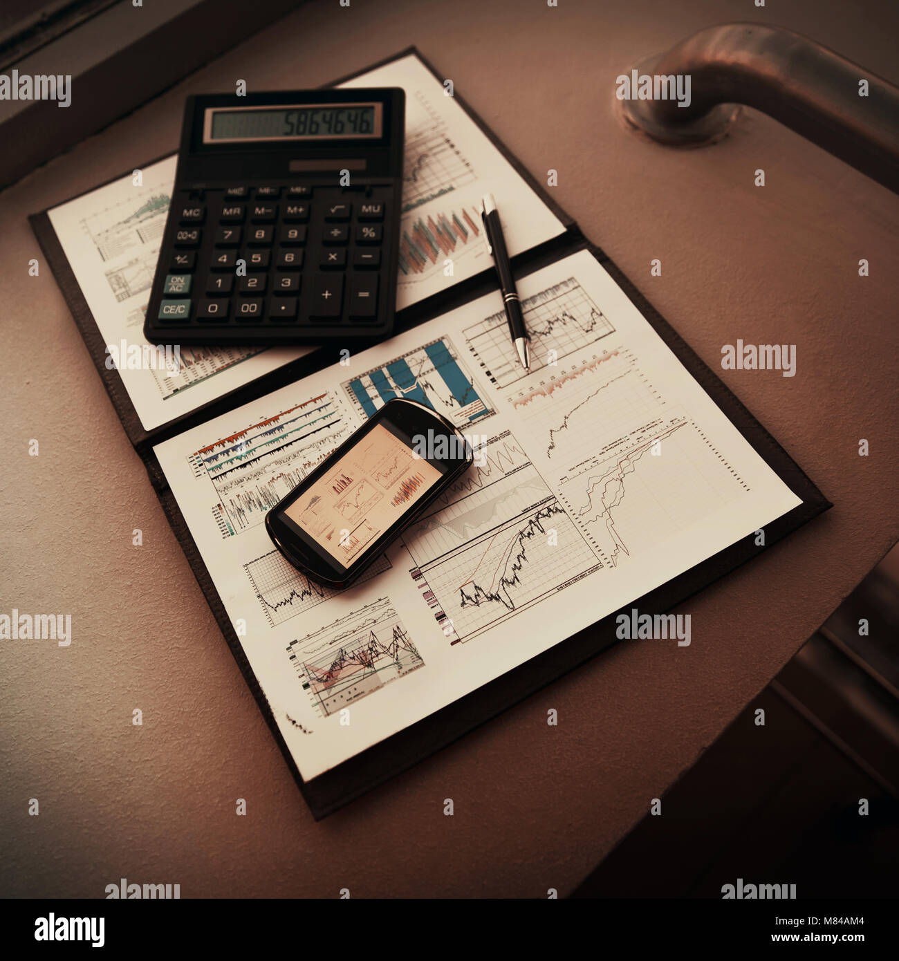 folder with the charts of financial analysis. Diagrams in the phone's screen, next is calculator and pen - Stock Image