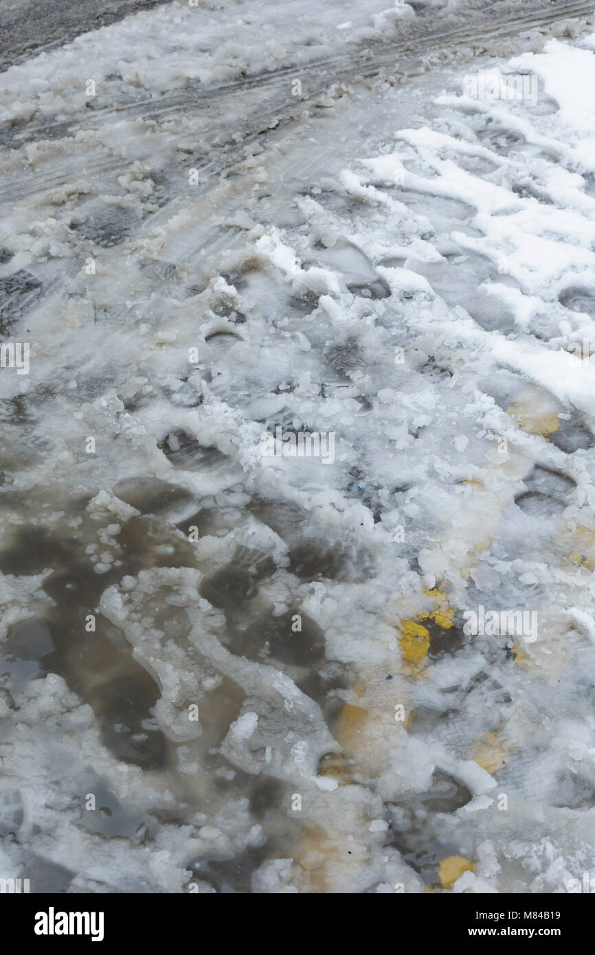 Partially visible Double Yellow Lines under sludge, sleet and snow on road, Woodhouse, Leeds, England. 8th March - Stock Image
