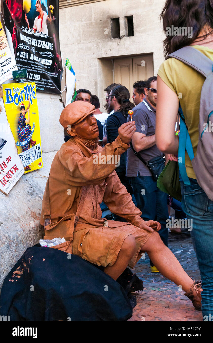 Avignon, France - July 24, 2011: The mime all painted ginger color from shoes till cap sitting on the street with - Stock Image