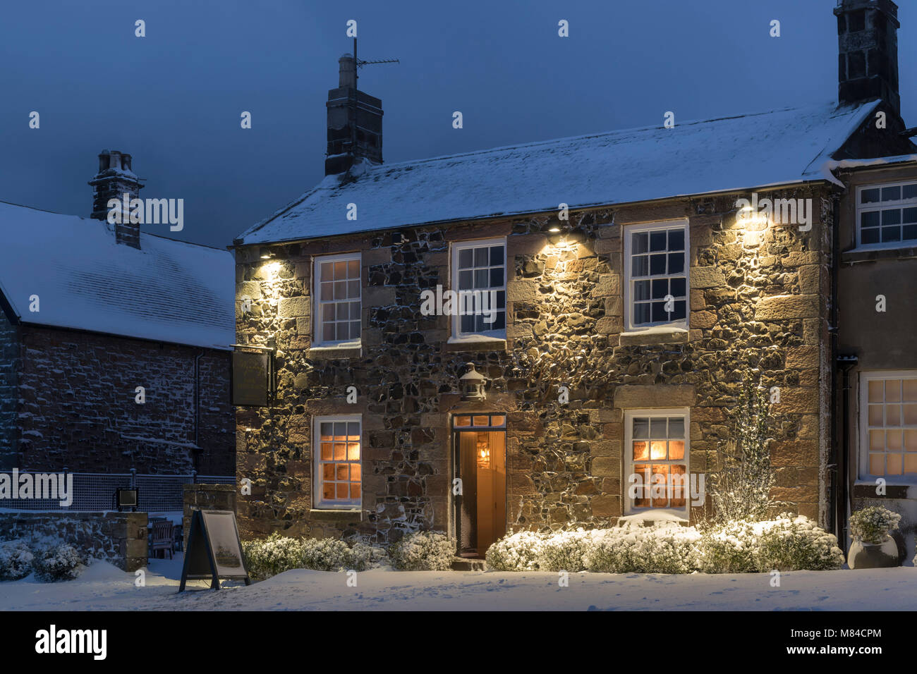 Welcoming village inn on a snowy winter evening, Bamburgh, Northumberland, England. Winter (February) 2018. - Stock Image