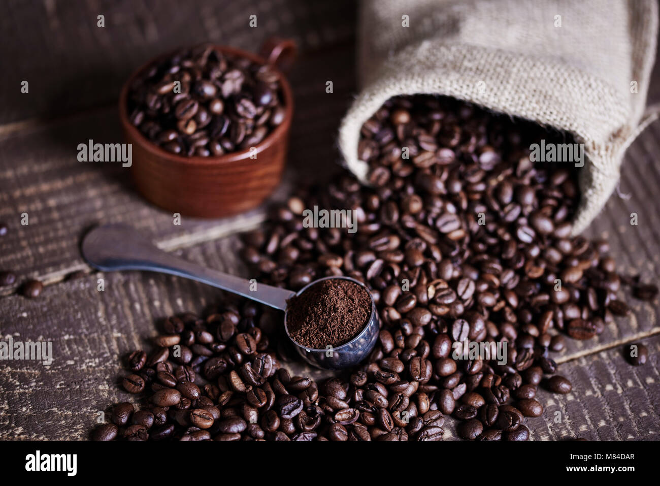 Beans of coffee and jute bag on wooden table - Stock Image