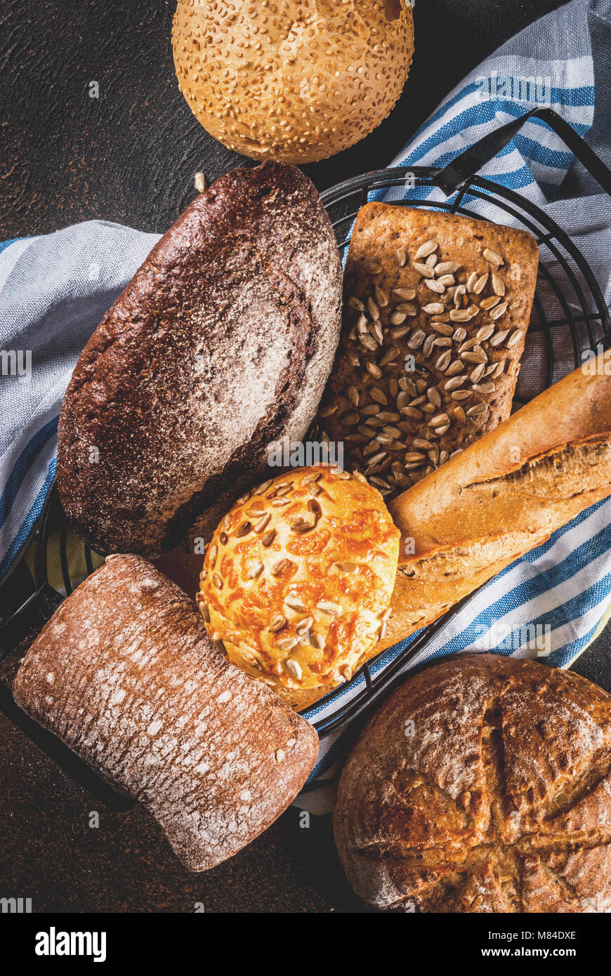 Variety of fresh homemade grain bread, in a metal basket, dark rusty background copy space top view - Stock Image