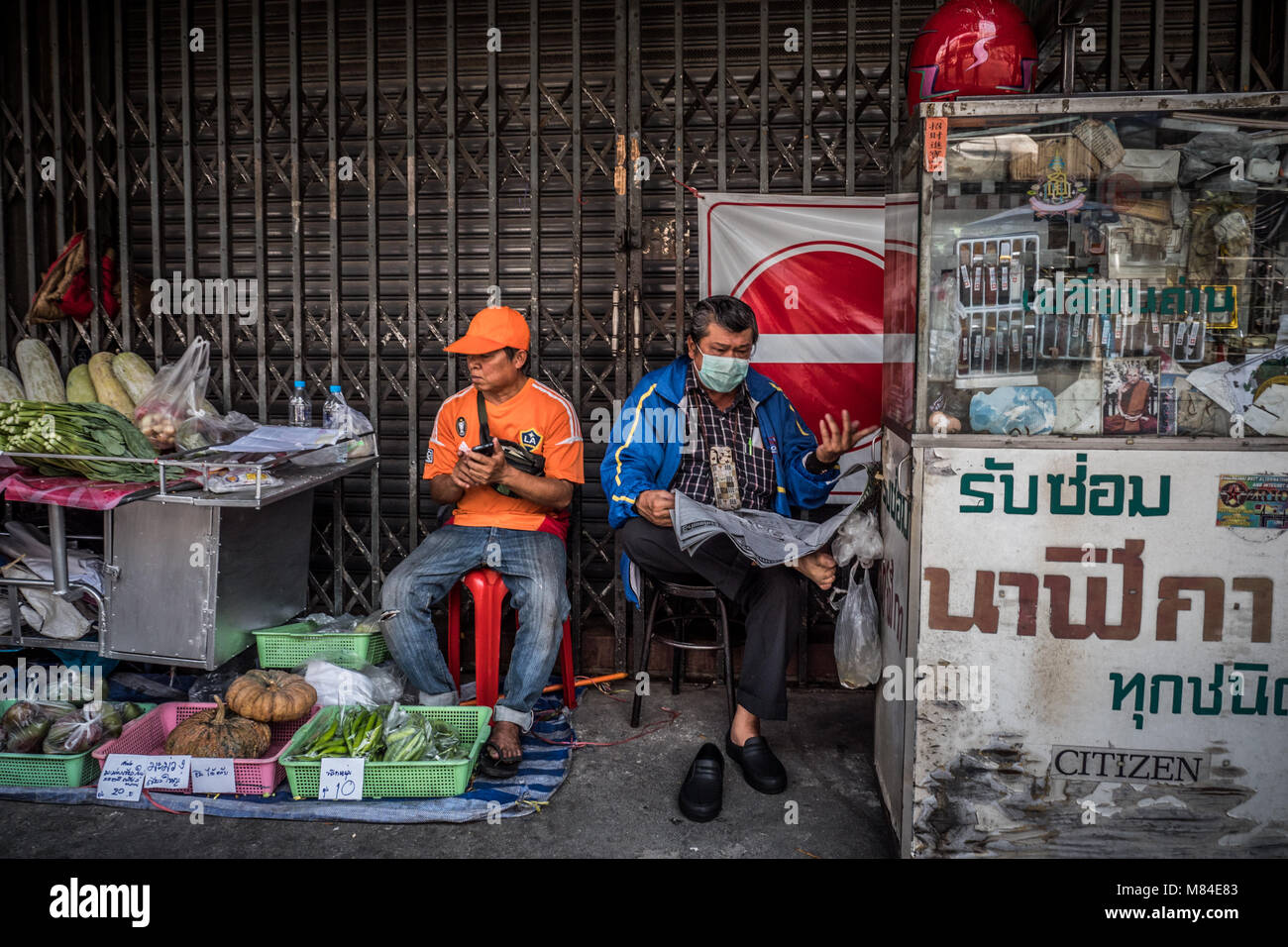 Two male market traders sat by their busines stalls, Chiang Mai, Thailand, South East Asia - Stock Image