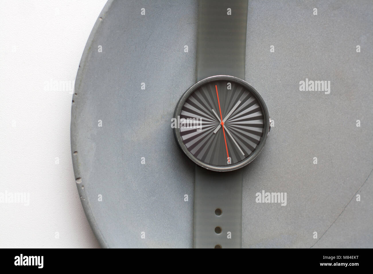 Time relativity: grey mechanical wrist watch without digits isolated on grey concrete plate from a high angle view - Stock Image
