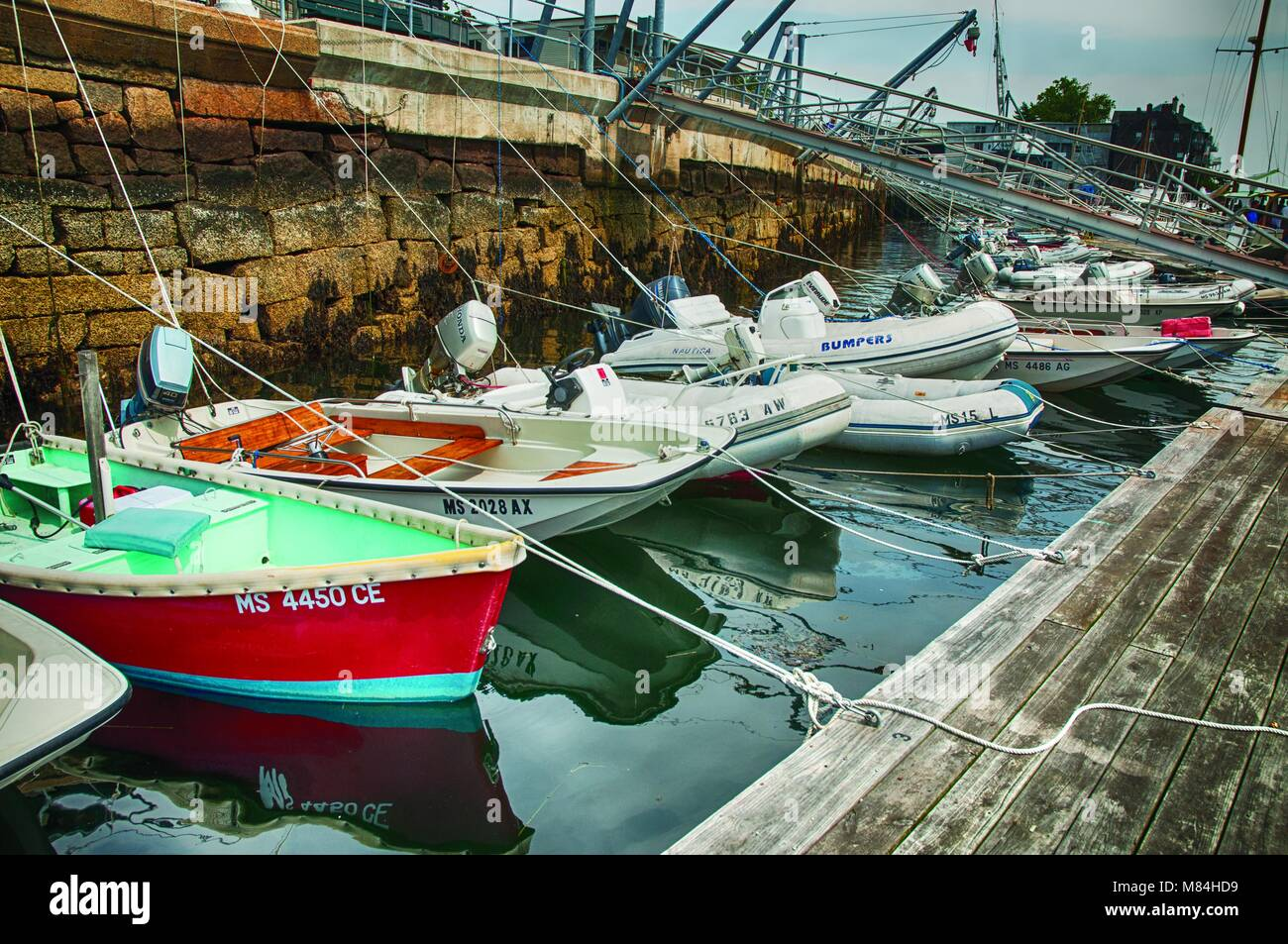 Small boats tied to dock by ropes for protection. - Stock Image