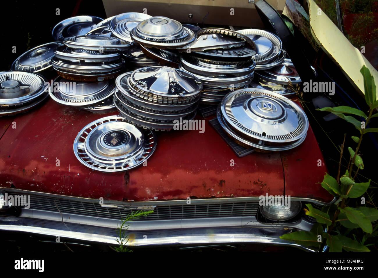 Hubcaps in pile at junkyard - Stock Image