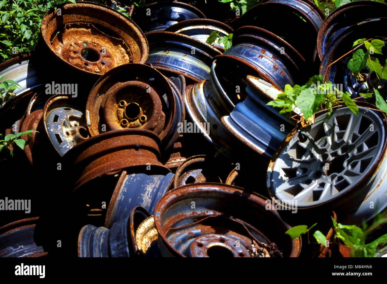 Wheel rims in pile at junkyard - Stock Image