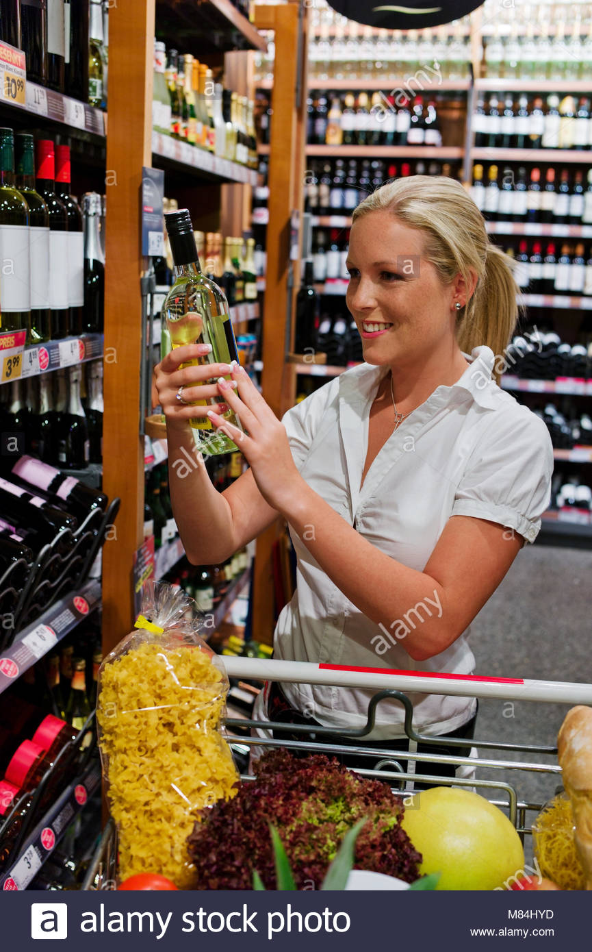 sale, shopping, consumerism and people concept - woman with food basket at grocery store or supermarket - Stock Image