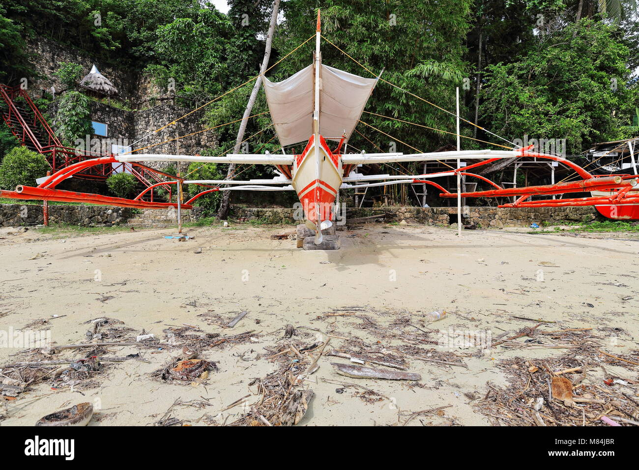 Balangay or bangka double-outrigger boat for touristic use of the nearby diving and snorkeling resorts beached on - Stock Image