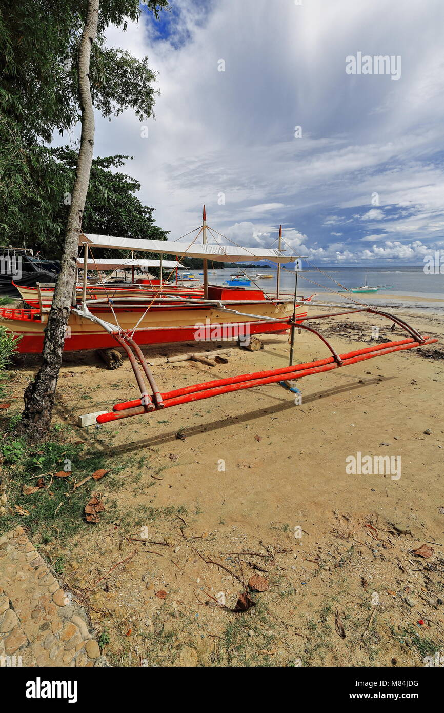 Balangay or bangka double-outrigger boats for touristic use of the nearby diving and snorkeling resorts beached - Stock Image
