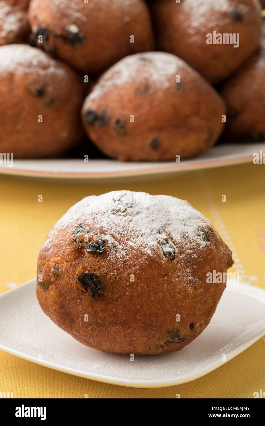 Single oliebol covered with sugar, traditional Dutch pastry for New Year's Eve and a heap at the background - Stock Image