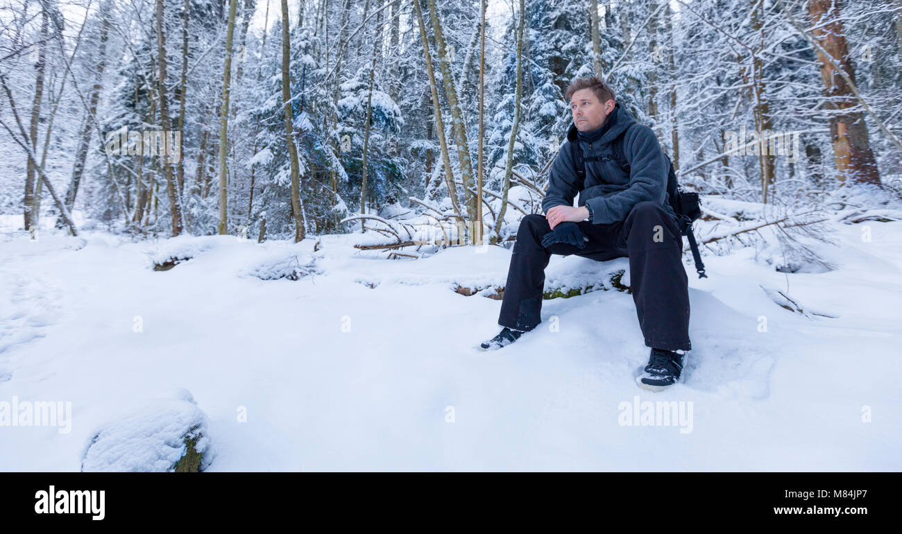 Adult male man sitting down in forest looking away into distance thinking in a winter landscape  Model Release: Stock Photo
