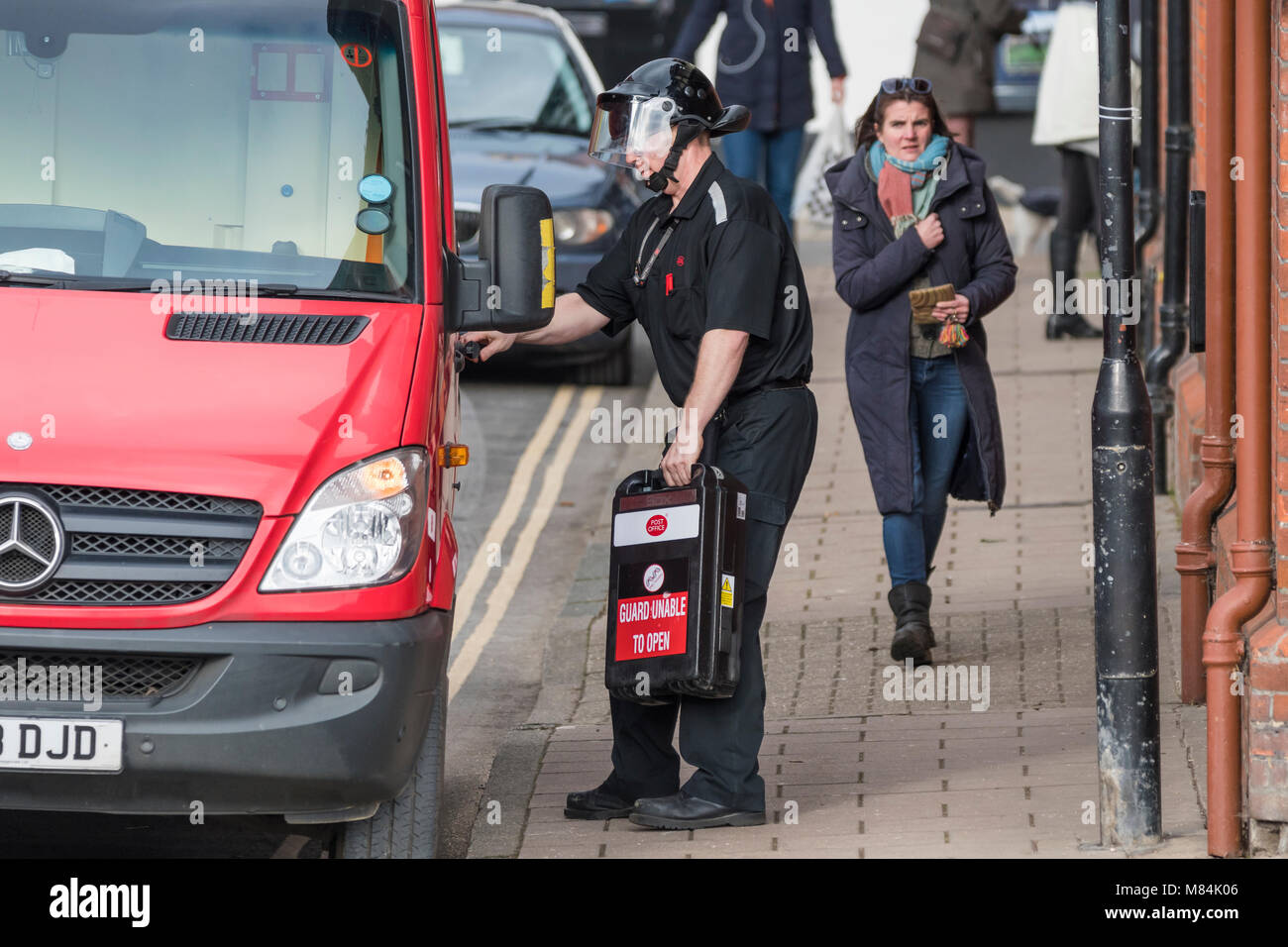 Male Post Office security guard in secure protective clothing carrying secure case to a van while delivering money - Stock Image