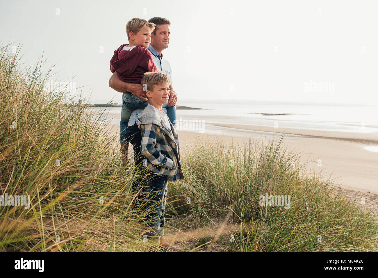 Single parent and his two sons looking at the beautiful view at the beach. - Stock Image