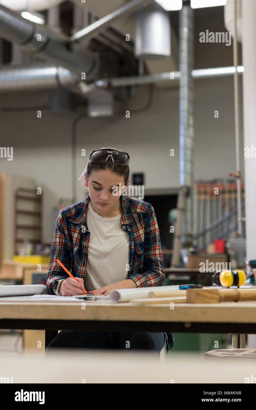 Female carpenter working at workshop - Stock Image