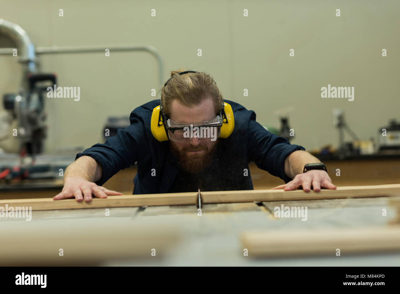 Male carpenter taking measurement of wood - Stock Image